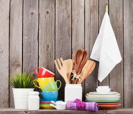 vintage kitchen: Kitchen utensils on shelf against rustic wooden wall