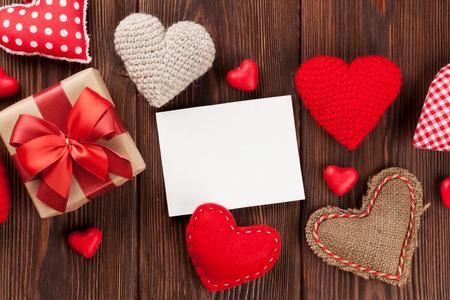 golosinas: Corazones de San Valentín día, caramelos, caja de regalo y tarjetas de felicitación sobre el fondo de madera. Vista superior con espacio de copia