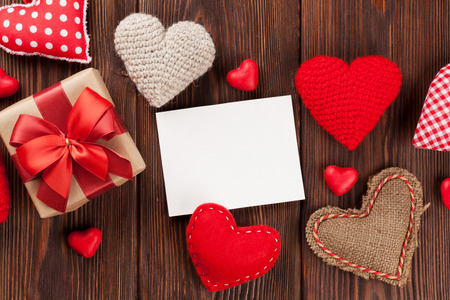 Valentines day hearts, candies, gift box and greeting card over wooden background. Top view with copy space