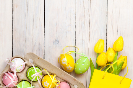 easter decorations: Easter background with colorful eggs and yellow tulips over white wood. Top view with copy space