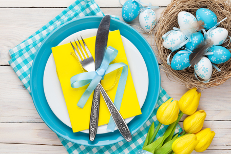 Easter with yellow tulips and colorful eggs over white wooden table. Top view