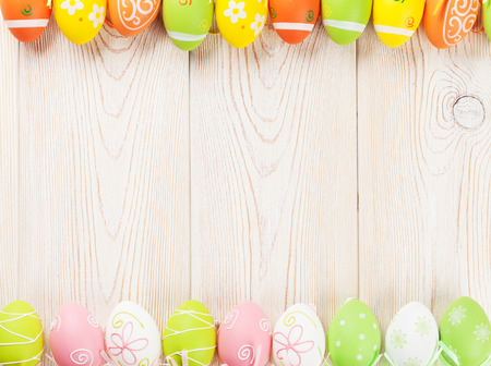 pastel: Easter background with colorful eggs over wooden table. Top view with copy space