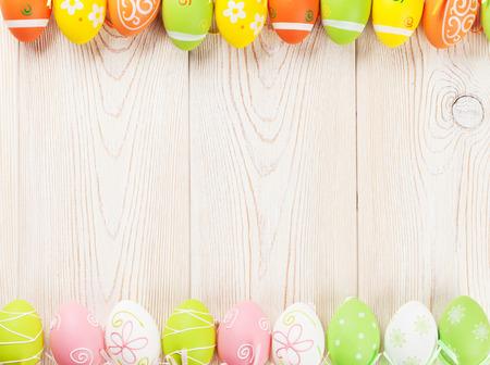 Ostern Hintergrund mit bunten Eiern über Holztisch. Ansicht von oben mit Kopie Raum
