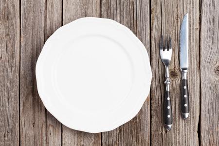 plato de comida: Empty plate and silverware on wooden table. Top view