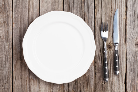 Empty plate and silverware on wooden table. Top view