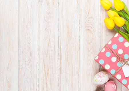 Pasen achtergrond met kleurrijke eieren en gele tulpen op wit hout. Bovenaanzicht met een kopie ruimte