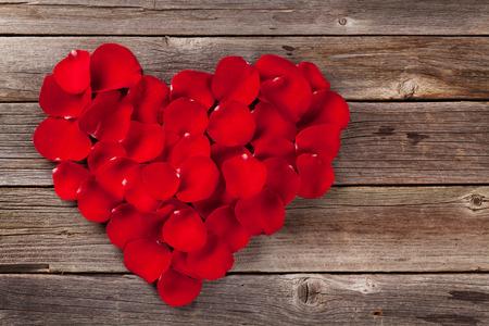 木製のテーブルの上の赤いバラの花びら心。コピー スペース平面図