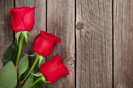 Rode rozen over houten tafel. Valentijnsdag achtergrond. Bovenaanzicht met kopie ruimte Stockfoto