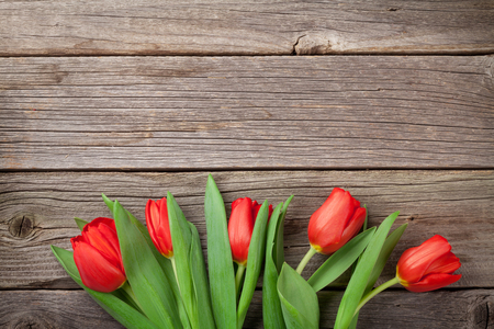 Red tulips over wooden table. Valentines day background. Top view with copy space