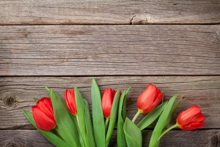 trompo de madera: tulipanes de color rojo sobre la mesa de madera. Fondo del día de San Valentín. Vista superior con espacio de copia