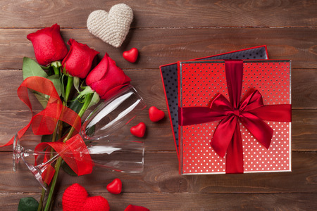 three gift boxes: Valentines day gift box and red roses on wooden table. Top view