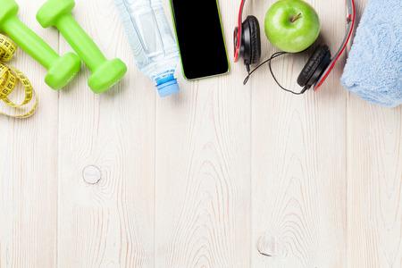 fitness: Halteres, garrafa de água, smartphones, fones de ouvido e fita métrica. Conceito da aptidão. Vista de cima, com cópia espaço