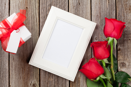 frame  box: Photo frame, red roses and Valentines day gift box over wooden table. Top view with copy space