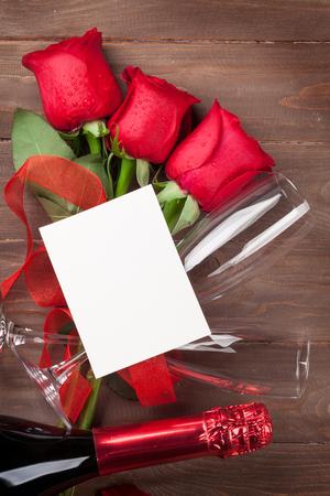 rosas rojas: Tarjetas de San Valentín saludo, champán y rosas rojas en mesa de madera. Vista superior con espacio de copia