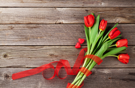red tulip: Red tulips and candy hearts over wooden table. Valentines day background. Top view with copy space