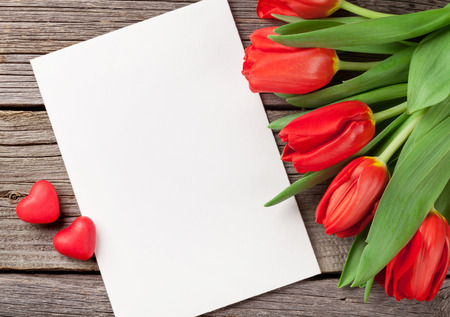 Red tulips, blank greeting card and candy hearts over wooden table. Valentines day background. Top view with copy space