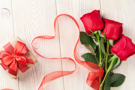 heart shaped box: Red roses, Valentines day gift box and heart shaped ribbon over wooden background