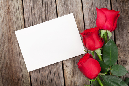 Red roses and Valentines day greeting card over wooden table. Top view with copy space Banque d'images