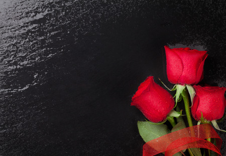 black stone: Red roses over black stone background. Top view with copy space Stock Photo