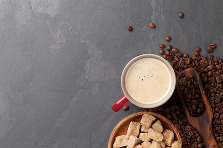 grano de cafe: Coffee cup, beans and brown sugar on stone table. Top view with copy space