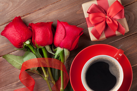 red gift box: Red roses, Valentines day gift box and coffee cup on wooden background. Top view