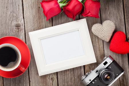 table: Photo frame, red roses, coffee cup and Valentines day hearts over wooden table. Top view with copy space