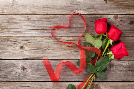 Red roses and heart shape ribbon over wooden table. Valentines day background. Top view with copy space Фото со стока