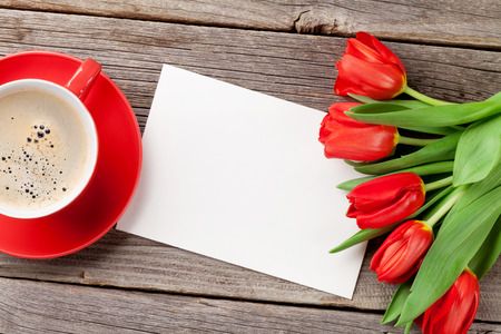 red tulip: Red tulips, Valentines day greeting card and coffee cup over wooden table. Top view with copy space Stock Photo
