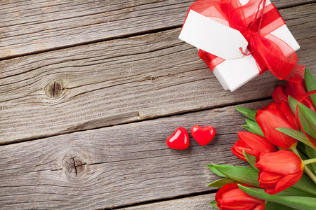 red gift box: Red tulips, gift box and Valentines day candy hearts on wooden table. Top view with copy space