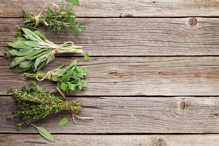 wooden aromatherapy: Fresh garden herbs on wooden table. Oregano, thyme, sage, rosemary. Top view with copy space Stock Photo