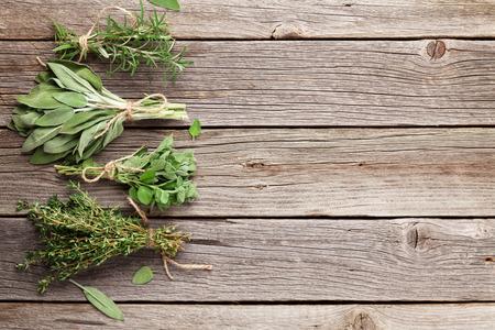 Verse tuinkruiden op houten tafel. Oregano, tijm, salie, rozemarijn. Bovenaanzicht met een kopie ruimte