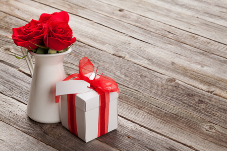 red gift box: Red roses and Valentines day gift box on wooden table. View with copy space