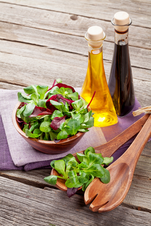 condiments: Corn salad leaves and condiments on wooden table. Valerianella locusta