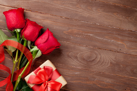 Red roses and Valentine's day gift box on wooden background. Top view with copy space