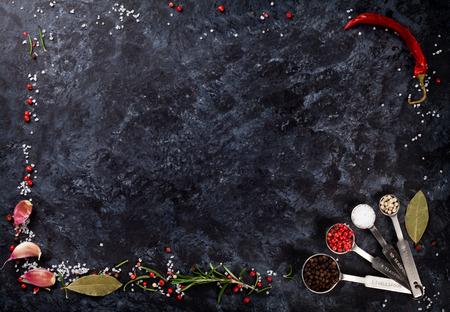 黒い石の背景にハーブやスパイスのフレーム。コピー スペース平面図 写真素材