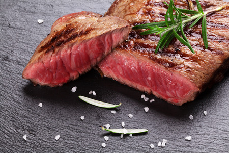 fillets: Grilled beef steak with rosemary, salt and pepper on black stone plate