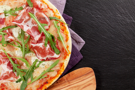 baked: Pizza with prosciutto and mozzarella on stone table. Top view with copy space
