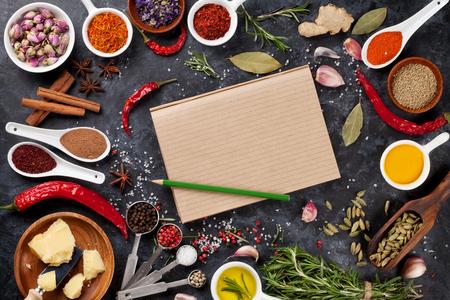 Bloc-notes pour votre recette avec des herbes et des épices sur fond noir en pierre. Vue de dessus avec copie espace