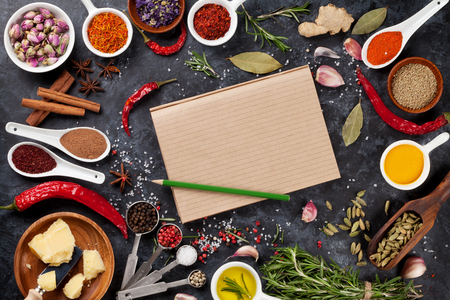 cooking: Notepad for your recipe with herbs and spices over black stone background. Top view with copy space