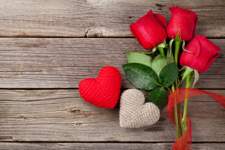 Red roses and Valentine's day hearts on wooden background. Top view with copy space