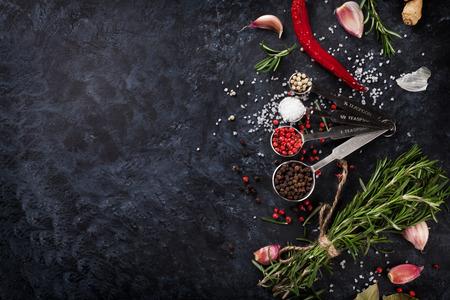 epices: Herbes et épices sur fond noir en pierre. Vue de dessus avec copie espace