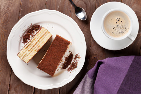 porcion de torta: Tiramisu dessert and coffee on wooden table. Top view