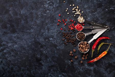 pepe nero: Colorful peppercorn e peperoncino sul tavolo in pietra. Vista dall'alto con lo spazio della copia