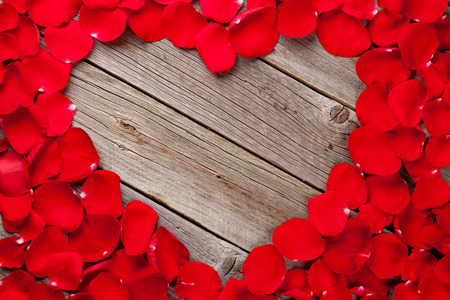Red rose petals heart over wooden table. Top view with copy space