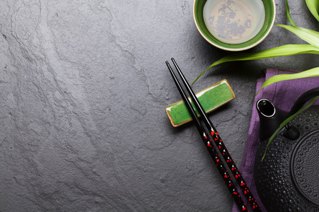 green background: Asian tea and teapot over stone table. Top view with copy space