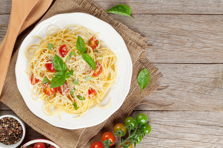 Spaghetti pasta with tomatoes and basil on wooden table. Top view with copy space