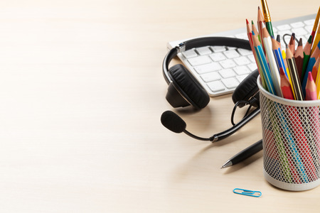 working desk: Office desk with headset laying on keyboard. Call center table. View with copy space Stock Photo
