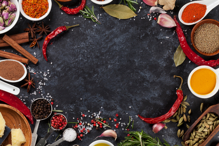 view top: Herbs, condiments and spices on stone background. Top view with copy space