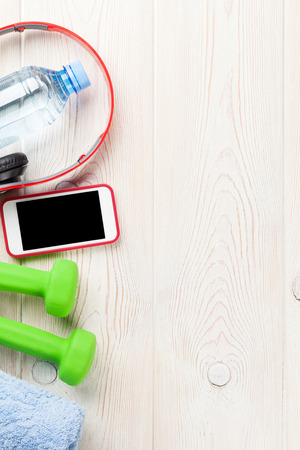 health and fitness: Dumbbells, water bottle, smartphone, headphones and towel. Top view with copy space
