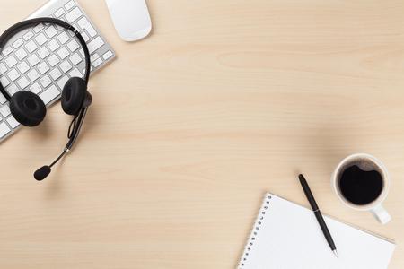 recepcionista: escritorio de oficina con auriculares y suministros. Llame a la mesa de soporte central. Vista superior con espacio de copia Foto de archivo